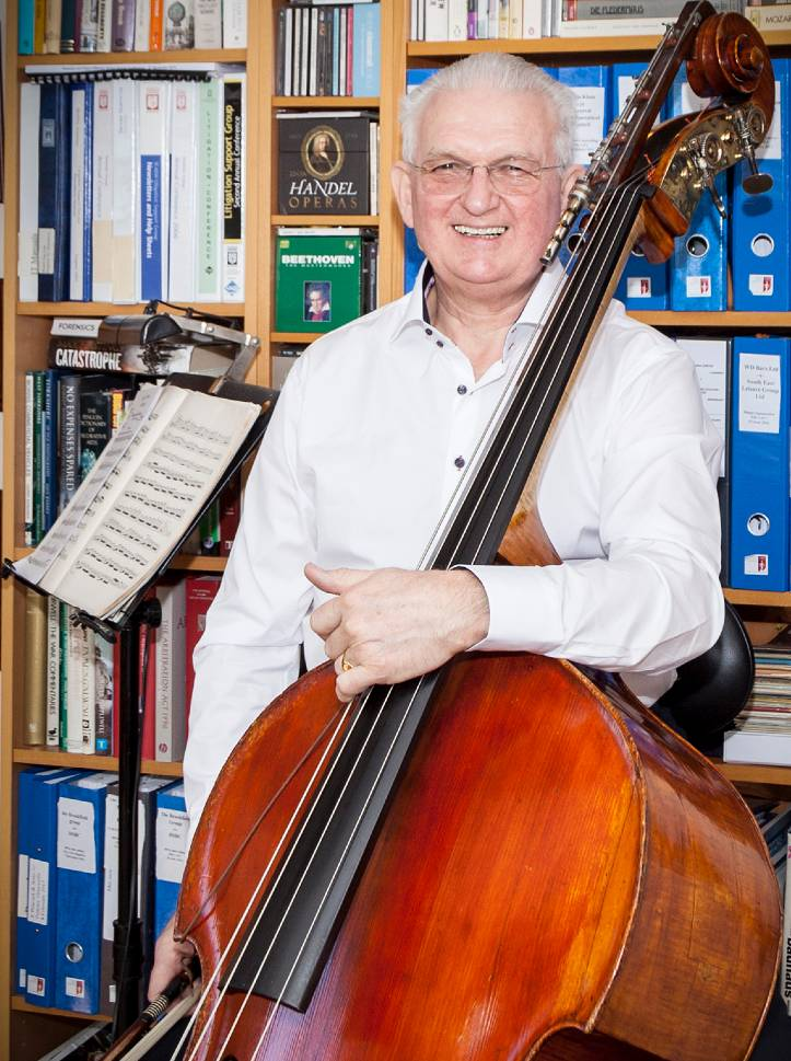 Chris Makin stood with his double bass in his office